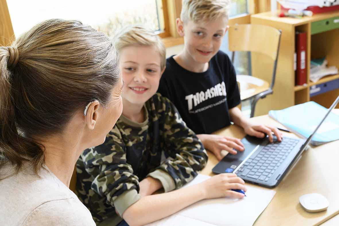 Lärare med hörapparat pratar med elever